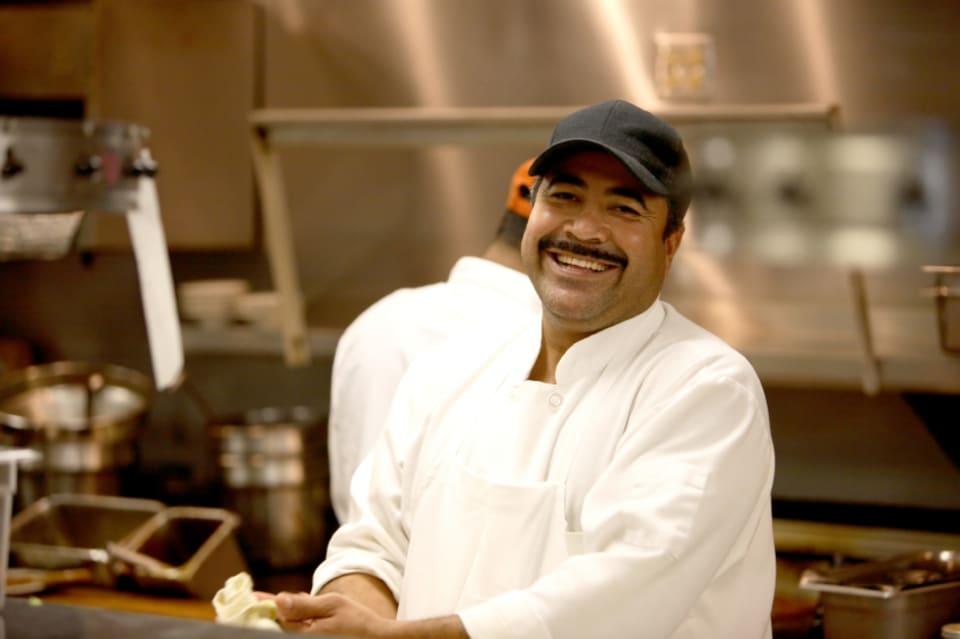 Gekleurde man werkt in keuken