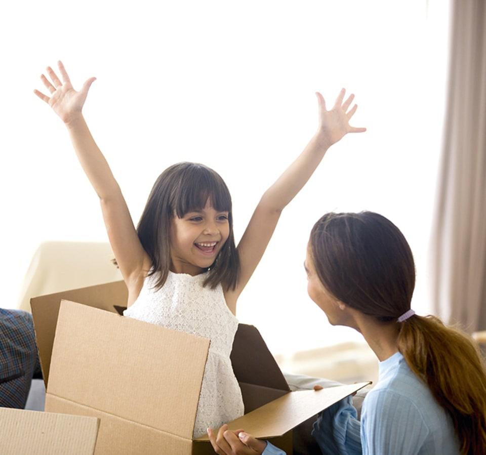 Juichend meisje verschijnt uit kartonnen doos