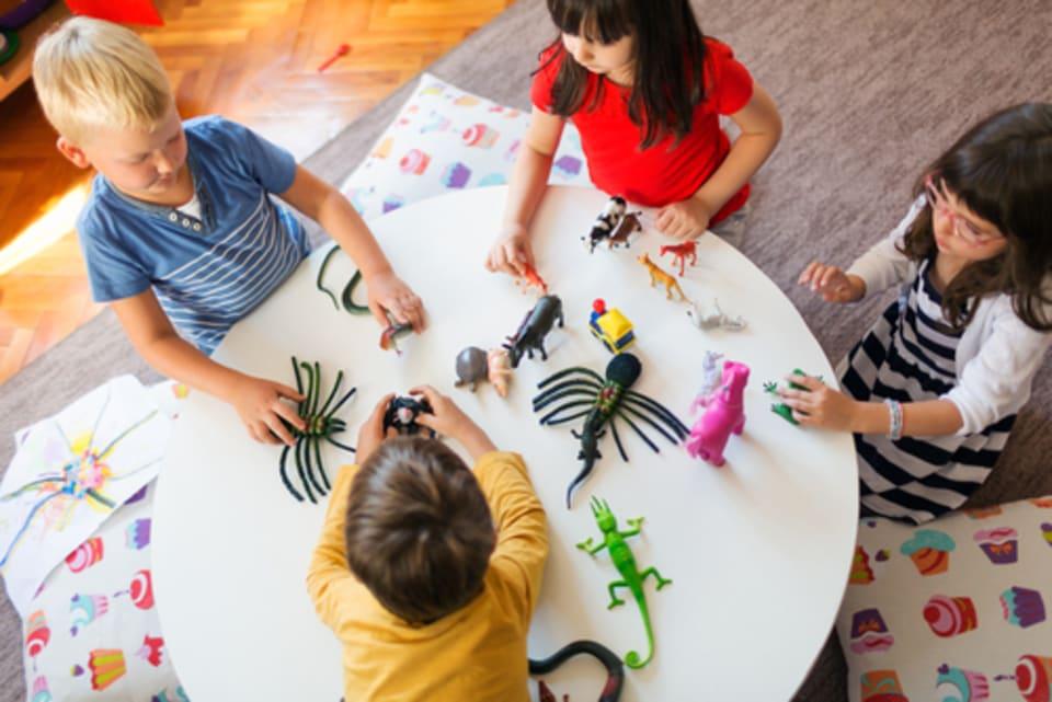 dierenwelzijn in de klas: vier kinderen aan tafel met speelgoeddieren