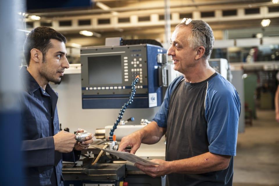 Jonge werknemer leert machine te bedienen in werkplaats